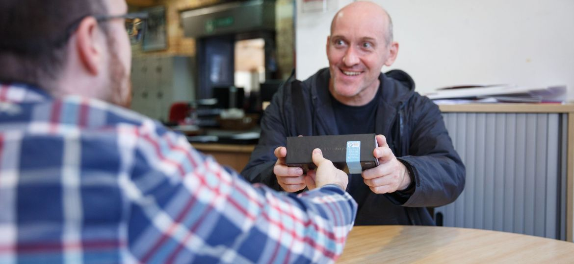 A man receiving a mobile phone from another man.
