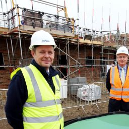 Two men standing in front of new homes under construction.