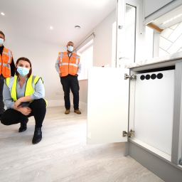 Three people wearing face masks in Thirteen's newly renovated 'smart' house in Middlesbrough.