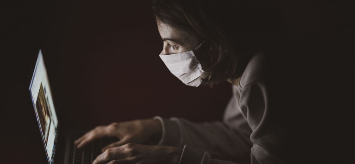 A woman wearing a face mask at her laptop in the dark.