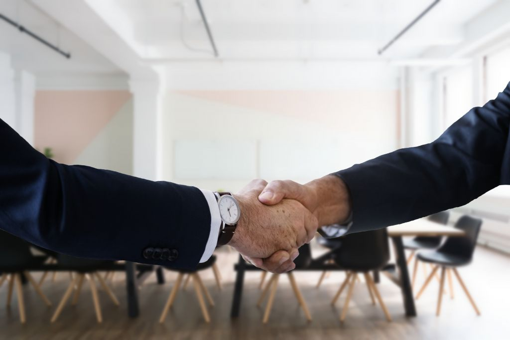 A man and a woman shaking hands in a meeting room.