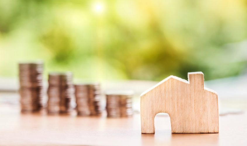A stock image of a wooden house in front of a stack of coins.