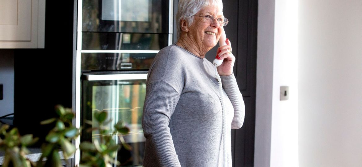 An older person on the phone in her kitchen.