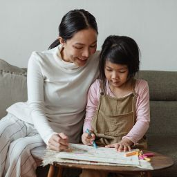 A mother sitting with her daughter on a sofa. The girl is colouring in.