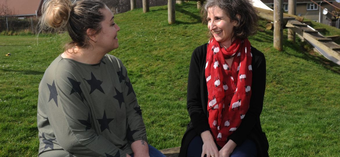 Two women sat speaking in the play area of a park.