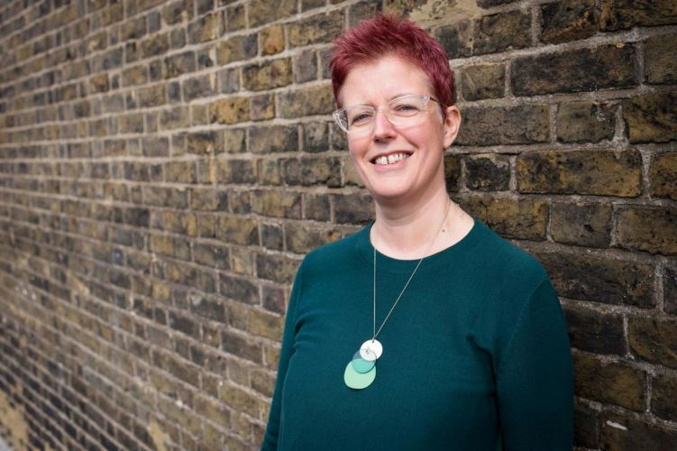Kate Dodsworth. She is smiling at the camera and wearing a green jumper. She is stood against a brick wall.