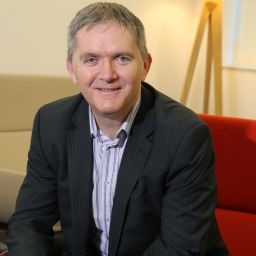 A portrait of Paul Fiddaman, the new chair of the Northern Housing Consortium's board. He is sitting on a red chair and smiling at the camera.