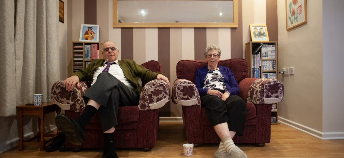 Two older people sitting on armchairs at home.