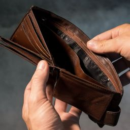 A man opening an empty wallet.