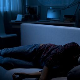 A male teen asleep on couch in front of TV,