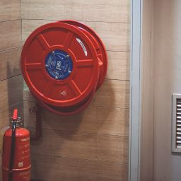 A fire extinguisher and a fire hose on the wall near a fire door.