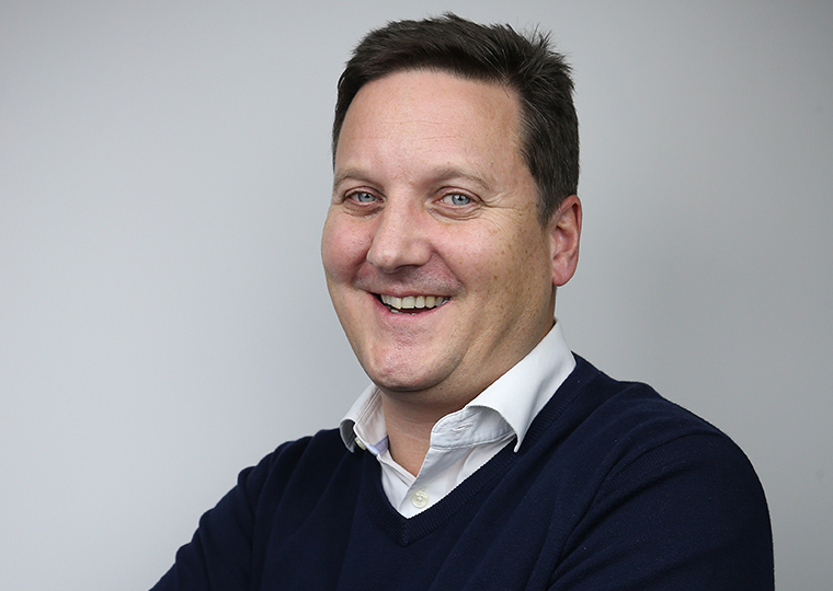 A portrait of Peter Luke is commercial director at the social housing data management company Illumar. He is smiling at the camera and is stood in front of a grey background.
