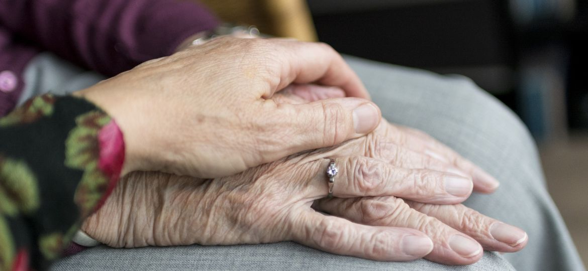 A woman holding the hands of an older person. Credit: Pixabay
