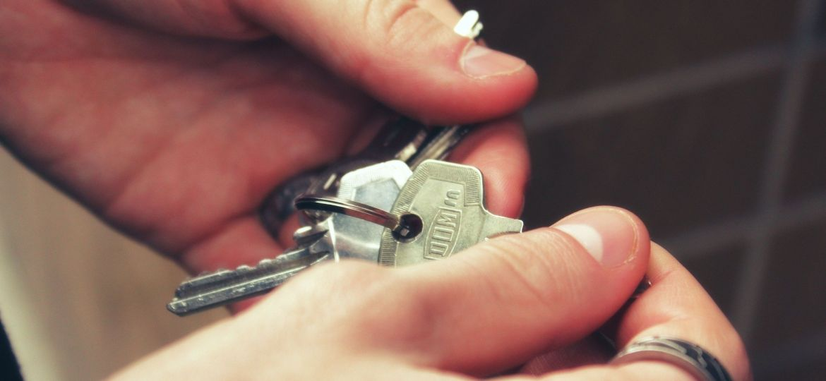 A person holding a set of house keys.