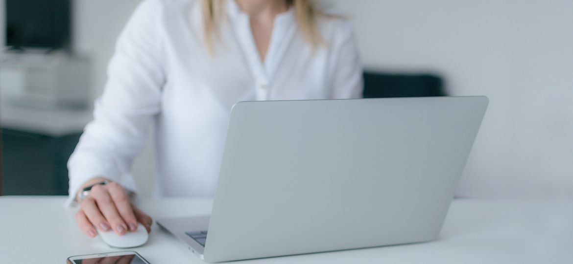 A woman sitting at a desk working on a laptop computer.