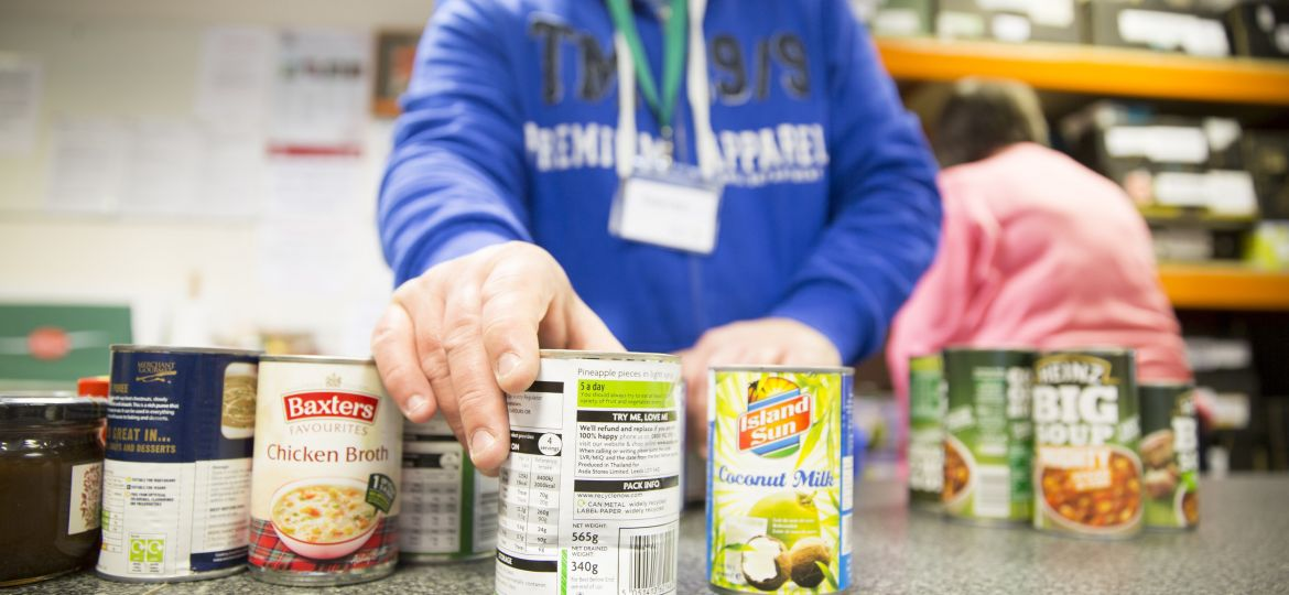 Tins of food with a volunteer at a food bank.