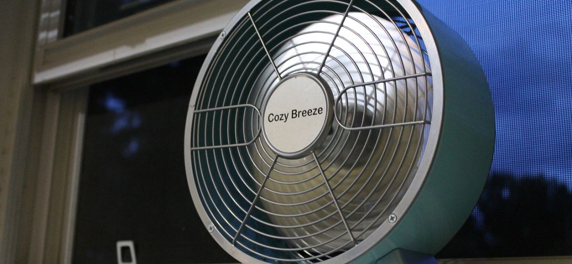 A fan wedged in the window of a residential building.